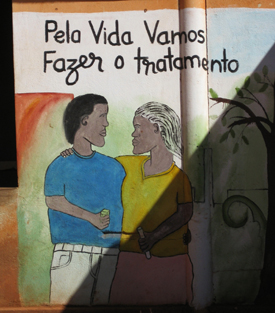 """""""For life, let's do treatment."""" AIDS awareness mural painting in Sussundenga, Mozambique. Photo: <a href=""""https://goo.gl/Mbf4wg"""">Ton Rulkens</a>/ Wikimedia Commons, 2007; cropped. <a href=""""http://goo.gl/mMLnuj"""">CC BY-SA 2.0</a>."""
