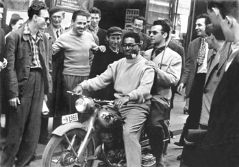 Dizzy Gillespie (left) and local musician Nikica Kalogjera (right) surrounded by fans while stradling a motorcycle in Zagreb, Yugoslavia (1956). Source: the Marshall Stearns Collection, Institute of Jazz Studies, Rutgers University.