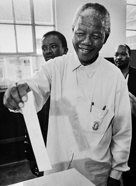"Nelson Mandela voting in 1994 election. (Photo: <a href=""https://bit.ly/3dxQejX"">Paul Weinberg via Wikimedia Commons</a>). <a href=""http://goo.gl/BUqs"">CC BY-SA 3.0</a>."