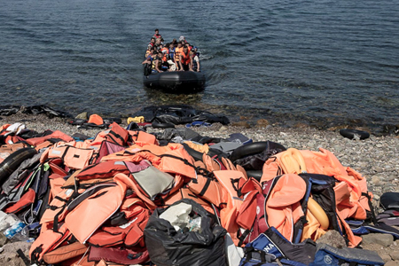 "September 2015. Refugees arrive on Lesvos from Turkey by dinghy, behind a huge pile of vests. (<a href=""https://goo.gl/M8DYue"">Photo: Freedom House, 2015</a>; cropped. Courtesy of Flckr.)"