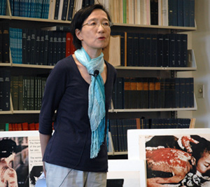 In front of photos of thermal radiation burn victims of the atomic bombings, Professor of Anthropology Mariko Tamanoi discusses the issue of radiation exposure.