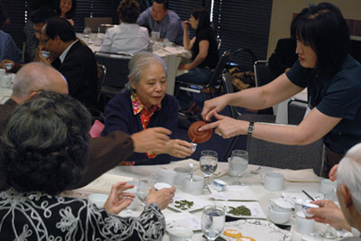 Lydia Kung of Eastrise Trading Corp. (right), an expert on tea varietals, directs side-by-side tastings for a group of UCLA supporters including Norma Lee. Seated around the same table are Howard Lee, Patsy Sung and Bob Sung.