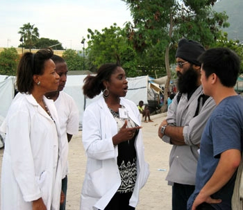 From right, Tu Tran, a UC Berkeley graduate and founder of UCHI, and Harrinder Singh, a pharmacy student at UCSF, speak to physicians at the Gheskio tent camp for displaced Haitians.